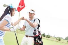 Amis masculins et féminins donnant le top-là au terrain de golf Images stock