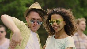 Amis masculins et féminins gais ondulant des mains, dansant dans des lunettes de soleil, lent-MOIS clips vidéos