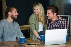 Amis masculins et féminins gais parlant dans le café Images libres de droits