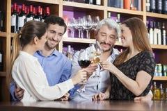 Amis masculins et féminins grillant des verres de vin Photos stock