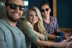 Amis masculins et féminins heureux à la table en café Image stock