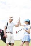 Amis masculins et féminins heureux donnant le top-là au terrain de golf Image libre de droits