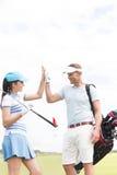 Amis masculins et féminins heureux donnant le top-là au terrain de golf Photographie stock