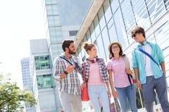 Amis masculins et féminins heureux marchant en dehors de l'immeuble de bureaux Photos stock