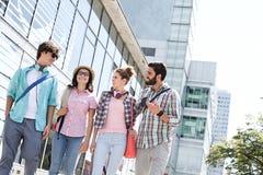Amis masculins et féminins heureux marchant en dehors de l'immeuble de bureaux Images stock
