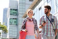 Amis masculins et féminins marchant en dehors de l'immeuble de bureaux le jour ensoleillé Images libres de droits