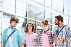 Amis masculins et féminins parlant à l'extérieur du bâtiment Photo stock
