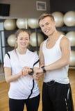 Amis masculins et féminins portant le gymnase de traqueur de forme physique Photos stock