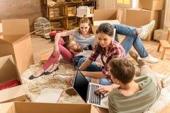 Amis masculins et féminins s'asseyant sur le tapis et à l'aide de l'ordinateur portable dans la nouvelle maison Photos libres de droits