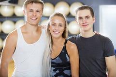Amis masculins et féminins sûrs souriant dans le gymnase Photographie stock