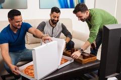 Amis masculins excités au sujet de la pizza Image libre de droits
