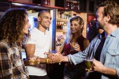 Amis masculins faisant la poignée de main au compteur dans le compteur dans le club Photos stock