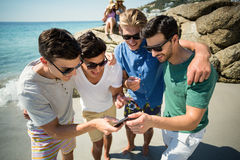 Amis masculins gais regardant dans le smartphone Photo stock