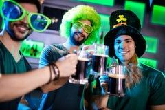 Amis masculins grillant des tasses de bière Photos stock