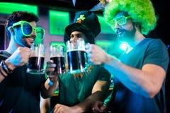 Amis masculins grillant des tasses de bière Photo libre de droits