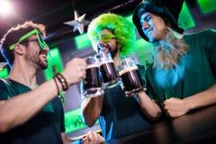 Amis masculins grillant des tasses de bière Photo stock
