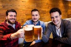 Amis masculins grillant la bière au restaurant Images libres de droits