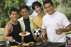 Amis masculins grillant tout entier la nourriture au parc Photographie stock libre de droits