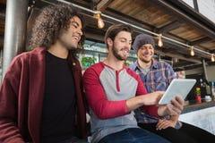 Amis masculins heureux à l'aide du comprimé numérique dans le restaurant Image libre de droits