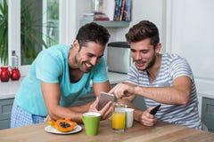 Amis masculins heureux à l'aide du téléphone Images libres de droits