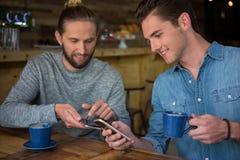 Amis masculins heureux à l'aide du téléphone intelligent dans le café Photos libres de droits