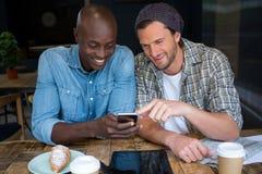 Amis masculins heureux à l'aide du téléphone portable dans le café Images libres de droits
