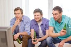 Amis masculins heureux avec de la bière regardant la TV à la maison Photo stock