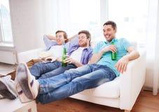 Amis masculins heureux avec de la bière regardant la TV à la maison Photographie stock