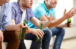 Amis masculins heureux avec de la bière regardant la TV à la maison Images libres de droits