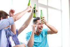 Amis masculins heureux avec de la bière regardant la TV à la maison Image libre de droits