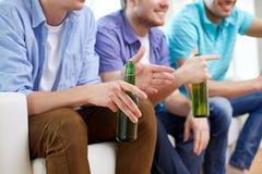 Amis masculins heureux avec de la bière regardant la TV à la maison Photo libre de droits