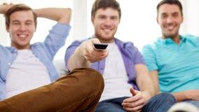 Amis masculins heureux avec la TV de observation à distance à la maison Photo libre de droits
