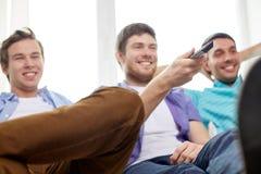 Amis masculins heureux avec la TV de observation à distance à la maison Images libres de droits