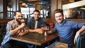 Amis masculins heureux buvant de la bière à la barre ou au bar Photo libre de droits