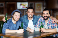 Amis masculins heureux buvant de la bière à la barre ou au bar Photo stock