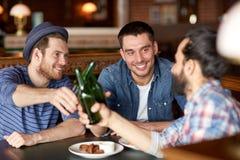 Amis masculins heureux buvant de la bière à la barre ou au bar Image stock