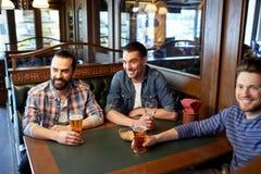 Amis masculins heureux buvant de la bière à la barre ou au bar Images libres de droits