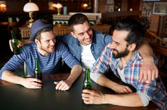Amis masculins heureux buvant de la bière à la barre ou au bar Photographie stock