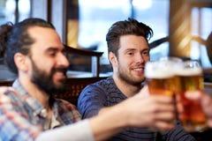 Amis masculins heureux buvant de la bière à la barre ou au bar Image libre de droits