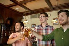 Amis masculins heureux buvant de la bière à la barre ou au bar Photos libres de droits