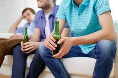 Amis masculins heureux buvant de la bière à la maison Photo libre de droits