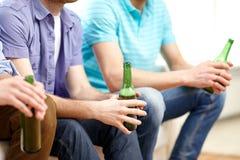 Amis masculins heureux buvant de la bière à la maison Photographie stock