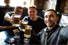 Amis masculins heureux buvant de la bière et prenant le selfie avec le smartphone à la barre ou au bar Photographie stock