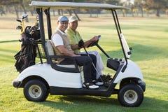 Amis masculins heureux de golfeur s'asseyant dans le boguet de golf Photos stock