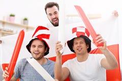 Amis masculins heureux encourageant et observant des sports à la TV Image stock
