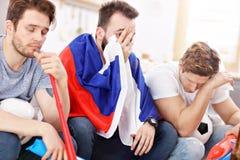 Amis masculins heureux encourageant et observant des sports à la TV Photographie stock libre de droits