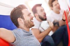 Amis masculins heureux encourageant et observant des sports à la TV Photo stock