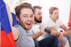 Amis masculins heureux encourageant et observant des sports à la TV Images libres de droits