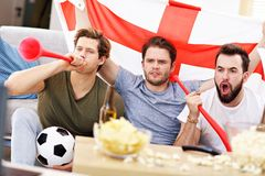 Amis masculins heureux encourageant et observant des sports à la TV Photographie stock