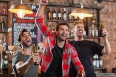 Amis masculins heureux encourageant tout en tenant des bouteilles à bière Images stock
